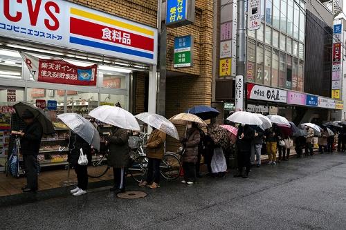 トイレットペーパーなど紙製品を買うため朝から並ぶ人々(写真:ロイター=共同)
