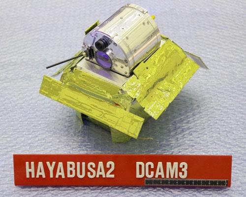 はやぶさ2から分離し、クレーター生成の瞬間を撮影したリモートカメラ「DCAM3」(画像:JAXA)。下は固定と放出を行うための台座。上の円筒形がDCAM3。「3」というのは、2010年に打ち上げた小型ソーラー電力セイル実証機「IKAROS」に、原型となるリモートカメラ「DCAM1」「同2」を搭載したため。