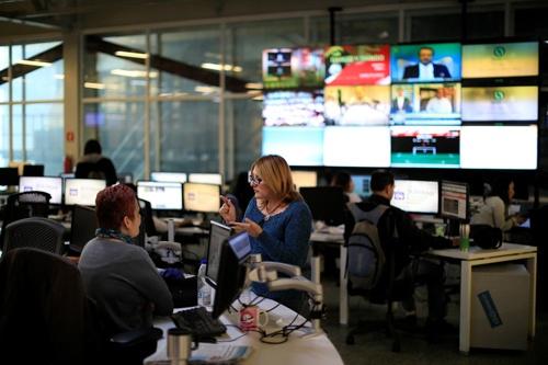 6月10日、フェイスブックとアルファベット傘下のグーグルはここ数年、規制当局や政界からの圧力を受け、世界各地の報道事業者に合計6億ドル(658億円)の支援を提供してきた。写真は2018年6月、カラカスの新聞社の編集フロアで撮影(2021年 ロイター/Marco Bello)