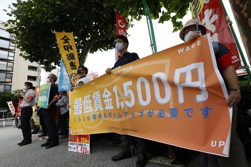 最低賃金の大幅引き上げを求めて気勢を上げる全労連関係者ら(写真:共同通信)