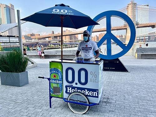 7月20日、欧米で新型コロナウイルスの制限措置が緩和され、酒好きの人たちはビールやワインを片手に祝っているかもしれないが、大手ビールメーカーが消費者に今売り込もうとしているのはノンアルコールビールだ。写真は15日、ニューヨークで行われたハイネケンのノンアルブール試飲ベントのスタンド(2021年 ロイター/Joyce Philippe)