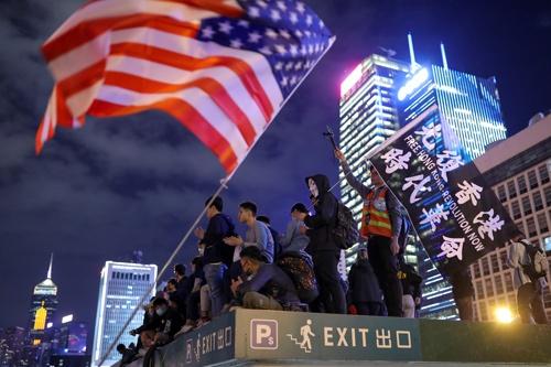 昨年の香港の抗議活動ではたびたび米国旗が掲げられた(写真:ロイター/アフロ)