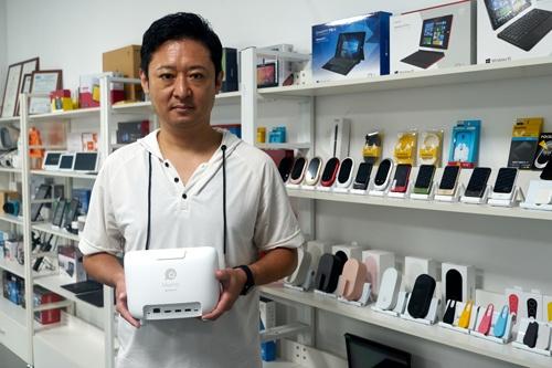 JENESISの藤岡社長。手にしているのはソースネクストから発売予定のリモート会議端末KAIGIO MeePet。新型コロナ禍でICT端末の需要は高まっている