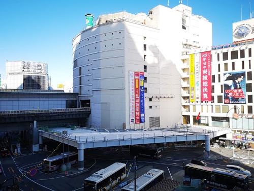19年12月に開業した渋谷フクラスから見た渋谷駅西口の空中デッキ。正面の東急東横店西館を沿うようにして建設されている。JR中央改札下の階段の前(右方、赤い矢印部分)から井の頭線との連絡通路(左方)に向けて伸びている。正面に見えるのが3月末で閉店する東急東横店西館。その右手が南館