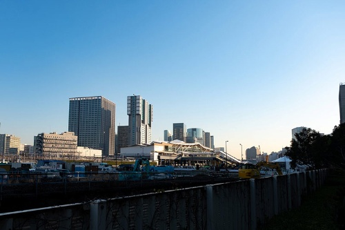 第一京浜側の線路脇から見た高輪ゲートウェイ駅(ビル群の手前中央)。駅舎は第一京浜から東側に140メートルほど入ったところにある