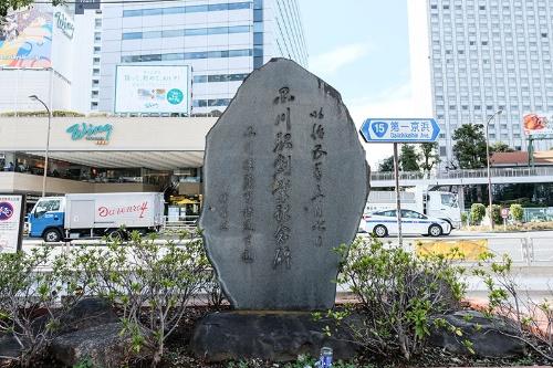 品川駅創業記念碑。駅の正面に立っている。後ろは第一京浜だ