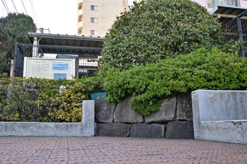 交差点の片隅に展示されている高輪海岸の石垣石。かつて東海道を支えていた