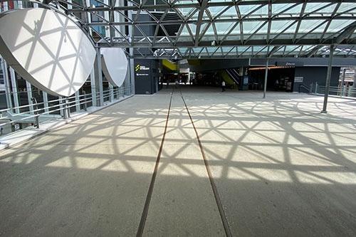 渋谷ストリームに向かう歩行者デッキ。かつての東急東横線の駅のデザインをモチーフしたものだ(写真左側)。足元には線路をイメージさせるラインが引かれており、その先の渋谷ストリーム内の通路には、一部本物の線路が埋め込まれている。これを見るとその上を律儀に歩きたくなる