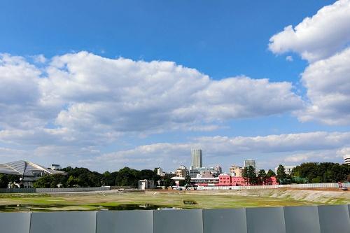 更地になった旧国立競技場跡地を南東から望む。右手にわずかながら残った斜面が顔を出している。左手に渋谷川西側の台地上に建つ東京体育館が見える