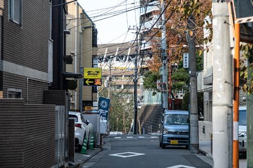 勢揃坂の上から国立競技場が顔を出す。先に見える横断歩道の先はさらに下っている。右手の電柱に「旧鎌倉街道」とあるのが見える