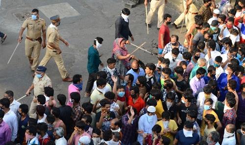 4月14日、インド南部の都市ムンバイで、全土封鎖の期間延長に抗議する出稼ぎ労働者と、移動制限を徹底させようと動く警察(写真:AP/アフロ)