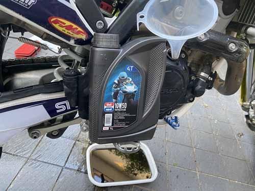 """ここのところ5回ほど連続して使っている<a href=""""https://unilopal.jp/lineup/racing/"""" target=""""_blank"""">ユニルオパールのRACING 10W-50</a>。ギアとエンジンの両方を冷却、潤滑するのですから、そりゃ負荷もかかろうというものです。オイルをケチるとバイク本来の性能を出すことができなくなります。昼飯はケチっても、ここをケチってはいけません。"""