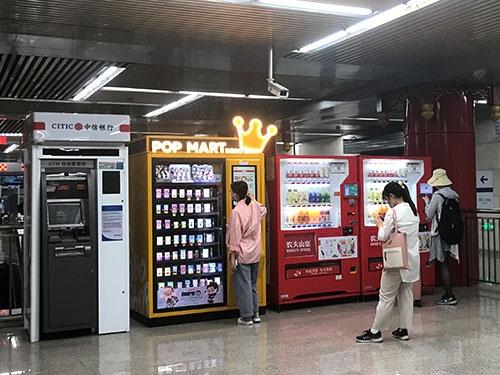 ポップマートの「盲盒(ブラインドボックス)」を購入、順番待ちする若い女性たち。ATMの利用者はいない。