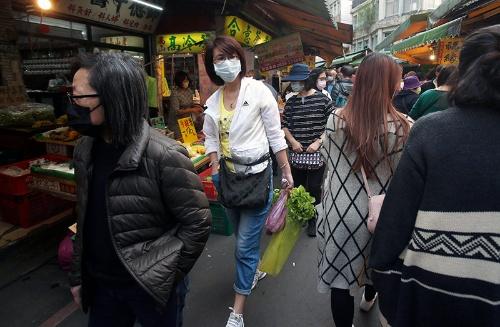 台北の市場でマスクして買い物する女性(写真:AP/アフロ)