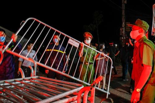 5月14日、ベトナム・ハノイ郊外の新型コロナウイルスに感染していた最後の村で、検疫のため設置していたバリケードを撤去する警察官(写真:ロイター/アフロ)
