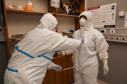 感染症の場合、医師や看護師は個人防護具をつける必要がある。写真はセルビアの病院(写真:ロイター/アフロ)