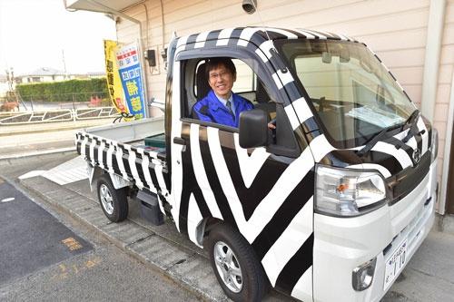 訪問営業車に乗るライフテクト イトウの伊藤社長。アドバイスを受けた東京都町田市の家電店ヤマグチに倣って、車の外装をゼブラ柄にしている(写真=菊池一郎、以下同)