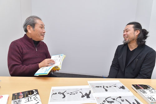 井上篤夫さん(左)が手にしているのは、前田鎌利さん(右)の著書『プレゼン資料のデザイン図鑑』。手前に見える井上さんの著書『孫正義 事業家の精神』の表紙には、鎌利さんが揮毫を寄せている(写真:菊池一郎)