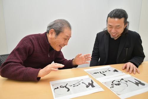 井上さんの著書の表紙に、鎌利さんが寄せた揮毫を眺めながら語り合う。孫社長に3案を提示し、選んだ1案は「孫さんのシャープさと柔らかさを表現した」(鎌利さん)という向かって左側の作品(写真:菊池一郎)