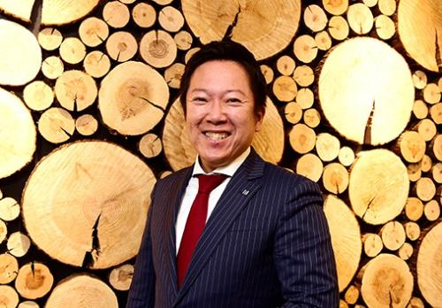 藤田氏は、社会課題を解決したいという思いで、まず地元、徳島県の那賀町での地方創生にも取り組んでいる。写真の、藤田氏の背景にあるのは、那賀町の材木資源・木頭杉をオフィスのインテリアにしたもの