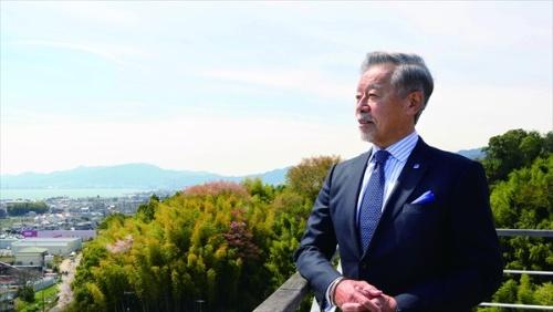 滋賀県大津市にある大型の生産拠点、「HORIBA BIWAKO E-HARBOR」のテラスに立つ堀場会長。「コロナショックで東京一極集中の脆弱さを感じた。この工場のような豊かな自然の近くで働くのもいいもの。今後は機能分散をもっと考えるべき」と話す(写真/宮田昌彦)