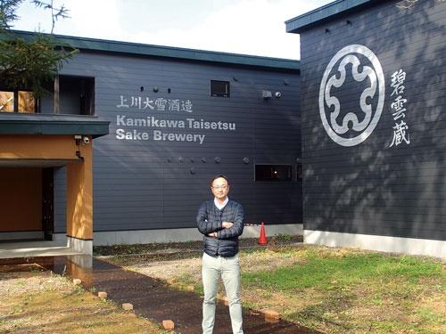 独特の戦略で後発ながら人気酒蔵になった上川大雪酒造の塚原社長。後ろは帯広畜産大学構内にある「碧雲(へきうん)蔵」