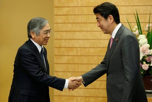 2018年4月、安倍晋三首相(当時、右)と握手する、再任された黒田東彦日銀総裁(左)。(写真:代表撮影/ロイター/アフロ)